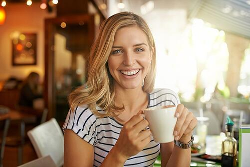 Woman in restaurant holding a coffee cup and smiling