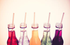 5 bottles of pop with straws sticking out