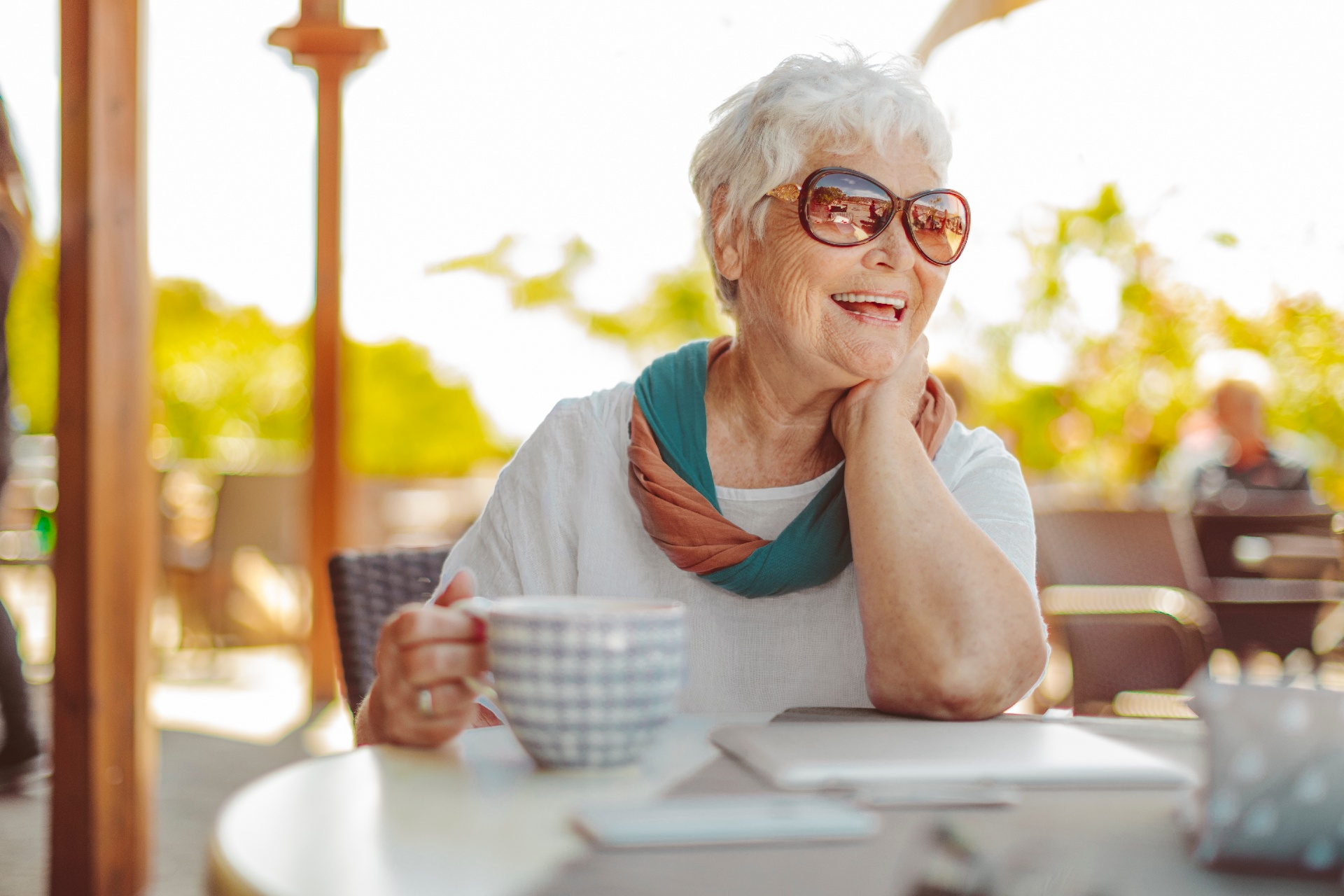 Older woman smiling and drinking coffee outdoors