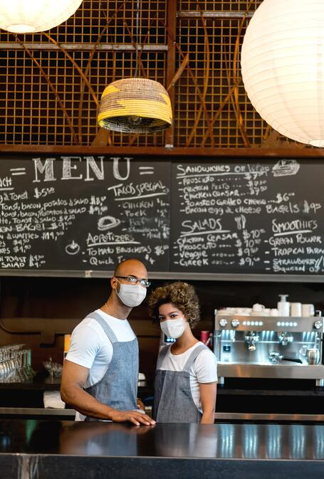 Two employees working behind the counter at a restaurant with masks on