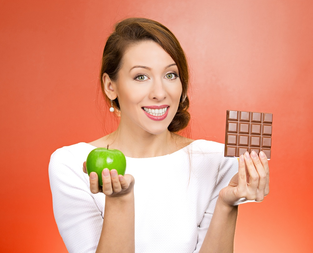 Closeup portrait, beautiful, smiling young woman offering nutritious lime apple as an alternative to unhealthy square milk chocolate, isolated red background. Food diet option situations, dilemma.