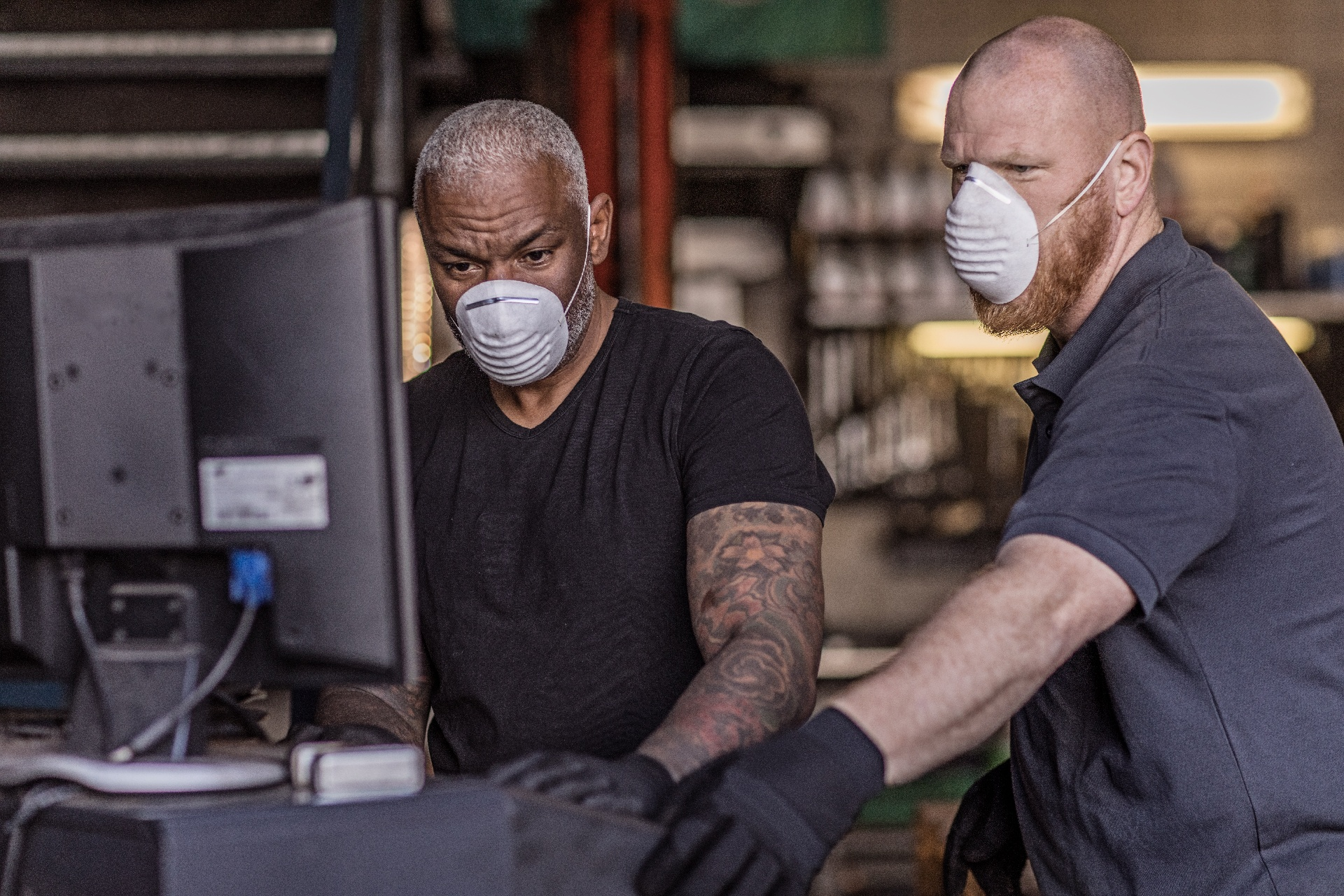 Two essential workers looking at a computer in the warehouse wearing masks