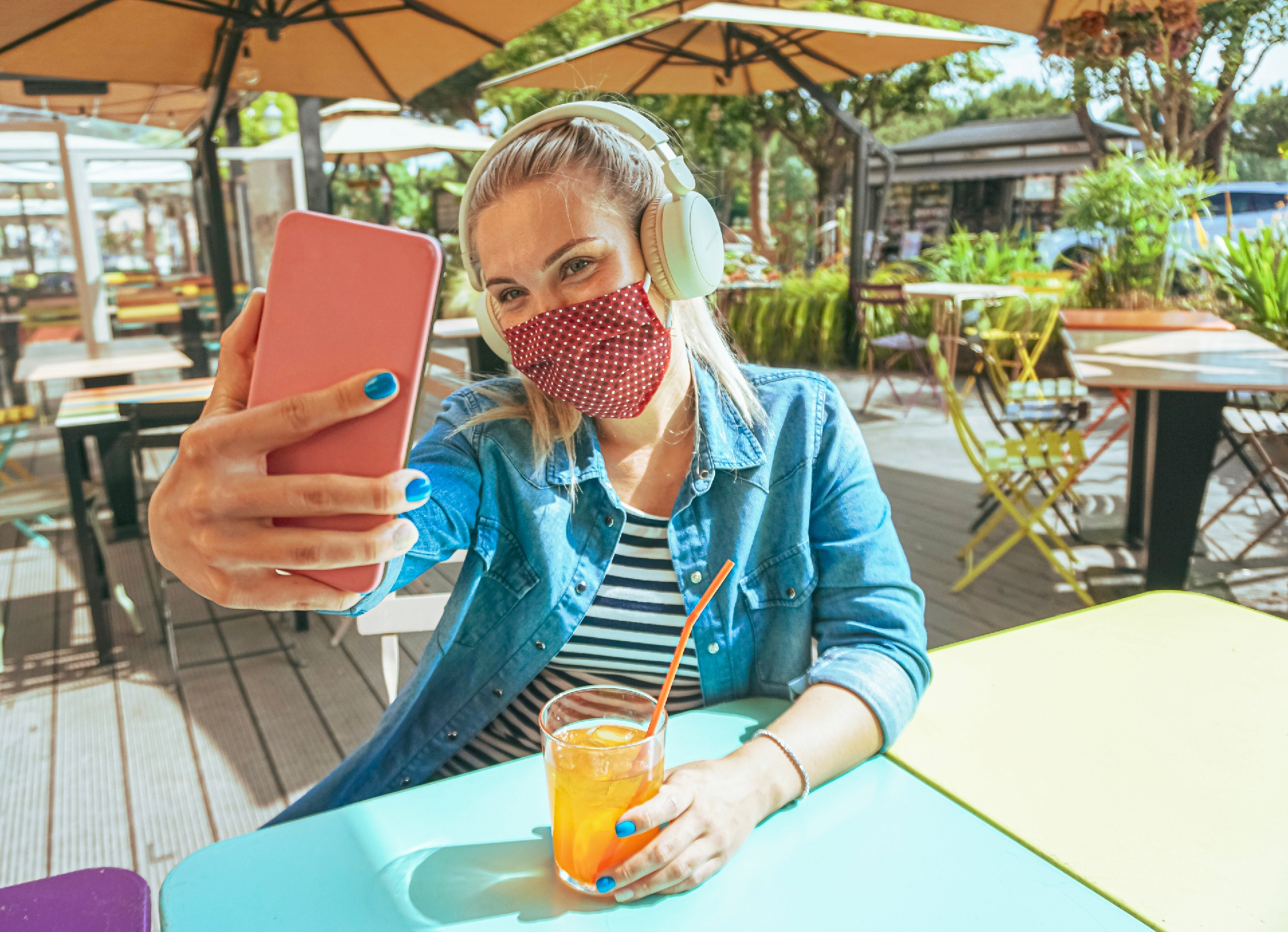 woman on an outdoor patio taking a selfie with a mask